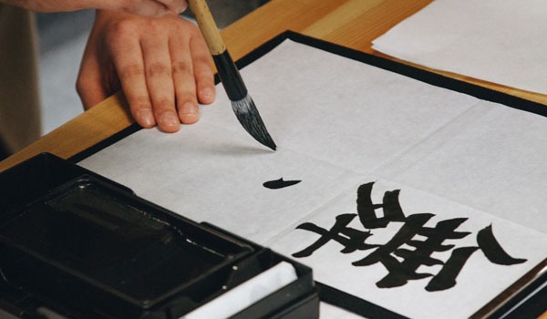 A man doing calligraphy with a paintbrush