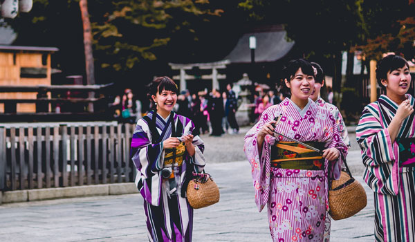 A group of women wearing kimonos at a temple